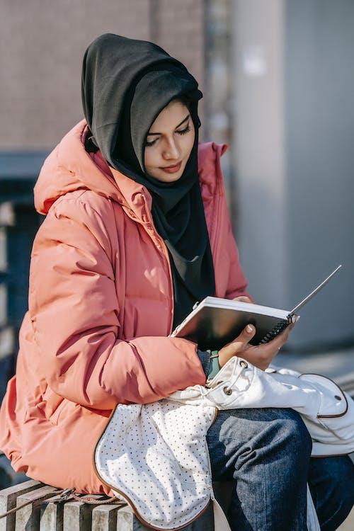Focused female student reading notepad on street
