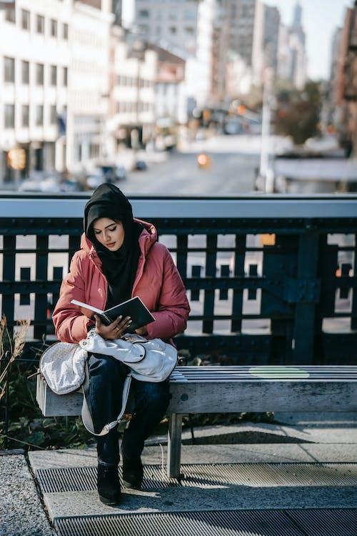 Wanita Berjubah Hitam Duduk Di Bangku Buku Bacaan