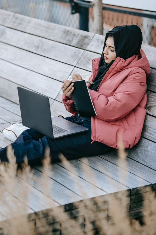 Wanita Berjubah Merah Menggunakan Komputer Laptop Hitam