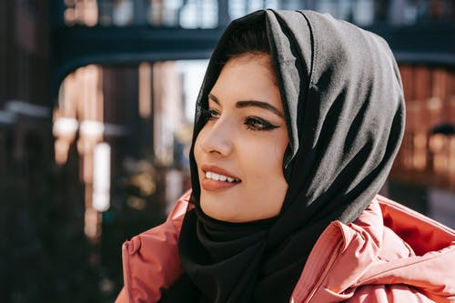 Content ethnic female in hijab smiling and looking away on blurred background of street