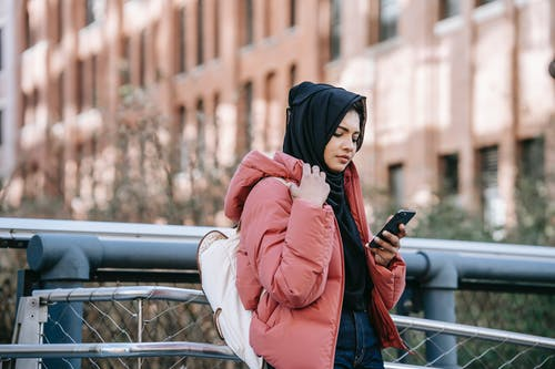 Muslim ethnic woman in hijab using smartphone on street
