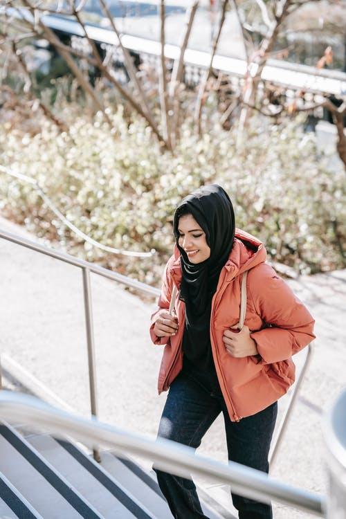 Muslim cheerful ethnic female in hijab and jacket promenading on urban stairs in daytime