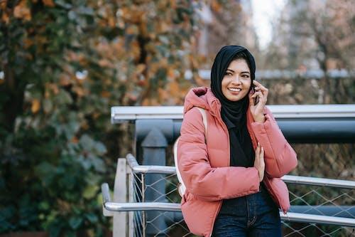 Muslim cheerful ethnic woman in hijab talking on smartphone