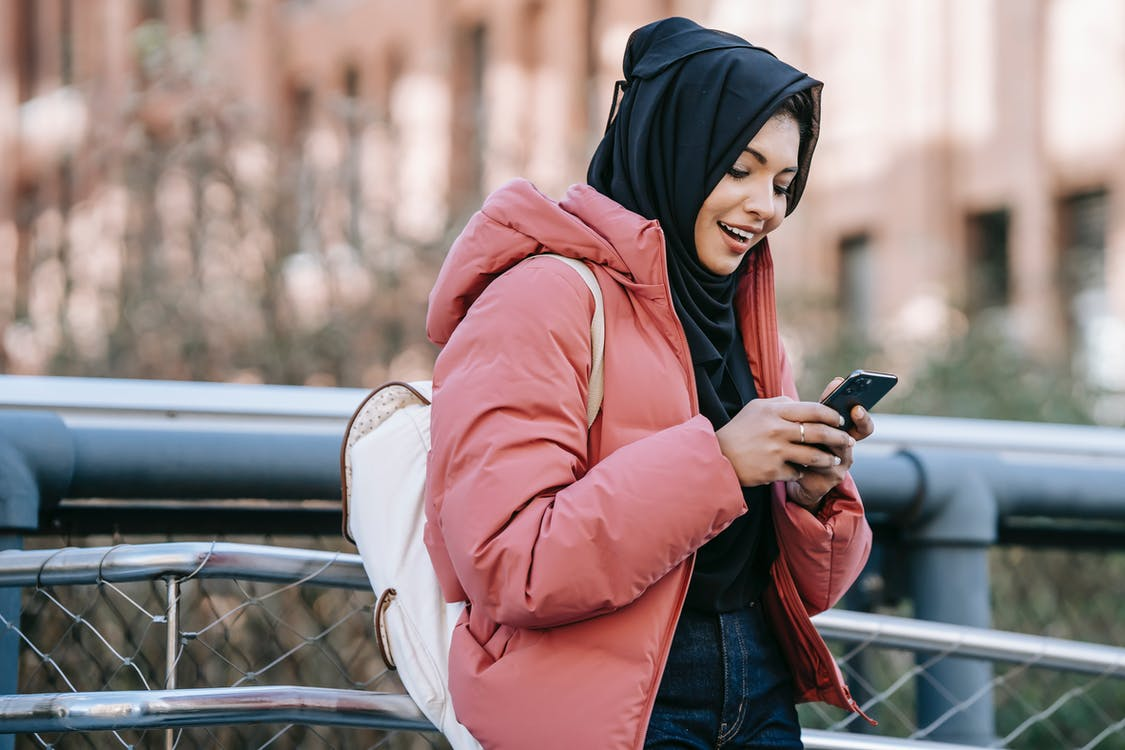 Muslim ethnic female in hijab texting message on mobile phone near iron construction on blurred background of building