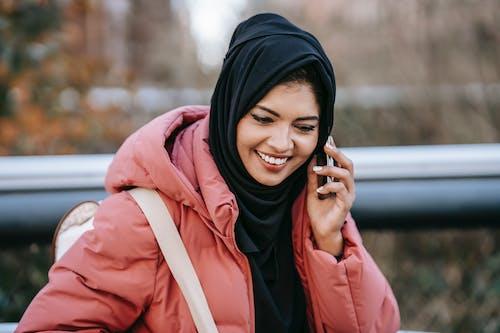 Muslim young ethnic woman in hijab talking on smartphone
