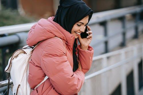 Positive Muslim female talking on smartphone on street