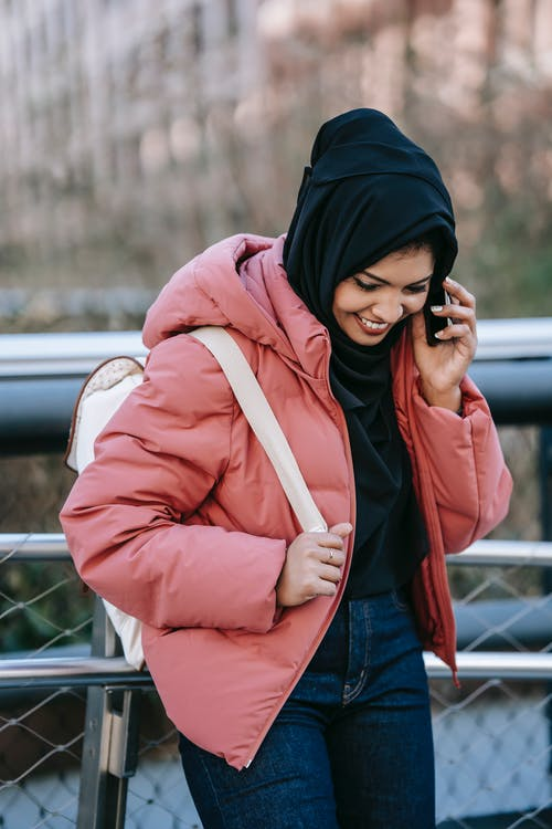 Smiling Muslim female in casual clothes and black headscarf standing near metal fence and talking on smartphone on street in daytime