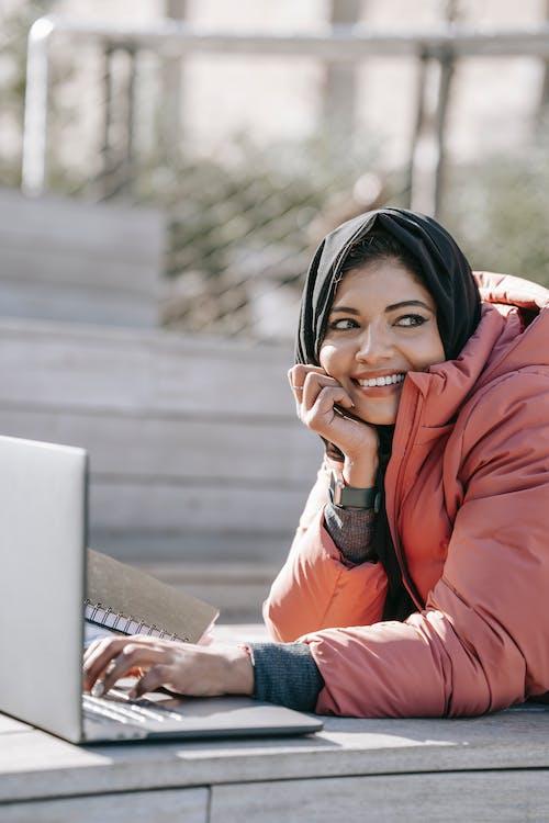 Positive Muslim female freelancer browsing laptop on street