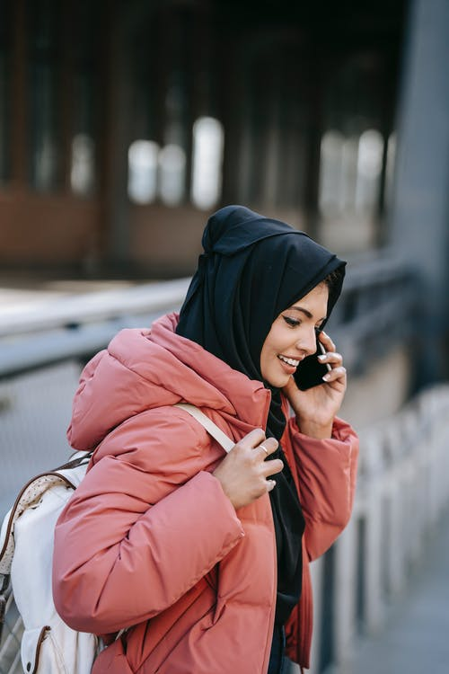 Cheerful Muslim female in casual clothes and black headscarf with backpack standing on street and talking on  smartphone on street in daytime