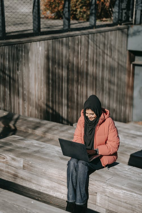 Cheerful Muslim woman sitting on wooden bench and using laptop