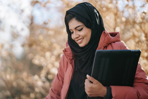 Smiling Muslim woman freelancer in black headscarf standing with netbook in hand and looking down on street against tree with autumn foliage in daylight