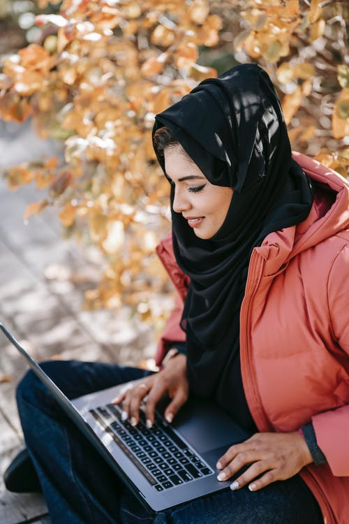 From above of focused Muslim woman freelancer in casual outfit and black headscarf sitting with netbook on knees while working on project on street against autumn tree in daytime