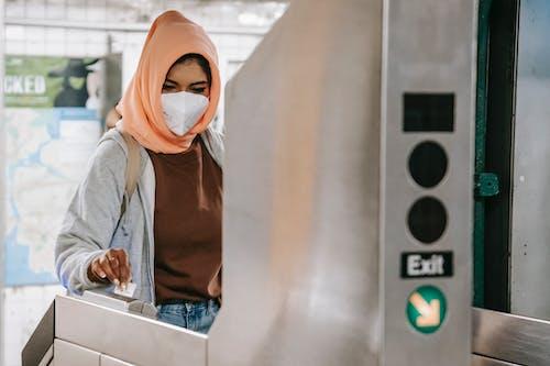 Pensive Muslim female in mask applying card to turnstile