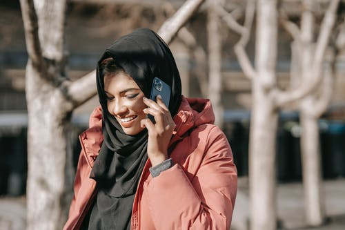 Happy Muslim woman in casual outfit and black headscarf speaking on smartphone against trees in park in daytime