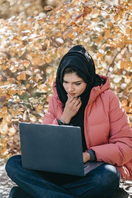 Pensive Muslim female using laptop on street against autumn tree