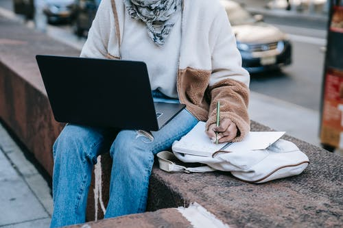 Orang Dengan Sweater Putih Dan Jeans Denim Biru Duduk Di Bangku Beton Abu Abu
