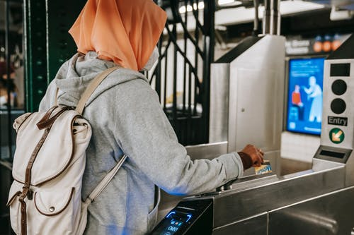 Back view Muslim woman in casual outfit and hijab with backpack using travel card for passing metro gate at daytime