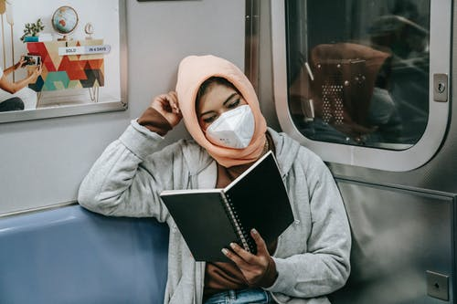 Faceless young Muslim ethnic woman in casual outfit and hijab with protective mask reading notebook while sitting in train in metro
