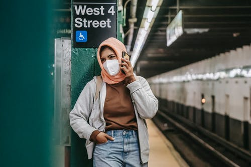 Faceless ethnic female standing in mask with cellphone in metro