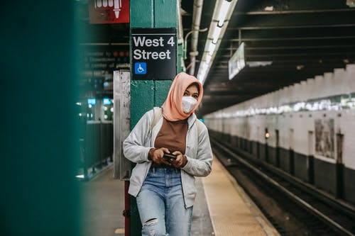 Faceless ethnic female standing in metro in mask with smartphone