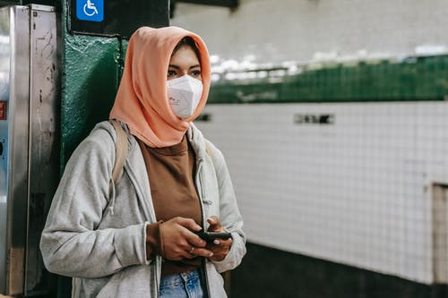 Faceless young Muslim ethnic woman in casual outfit with protective mask and hijab leaning on column in metro station while surfing on smartphone and looking away while waiting for train