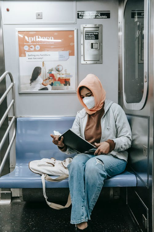 Anonymous ethnic female sitting in mask in train