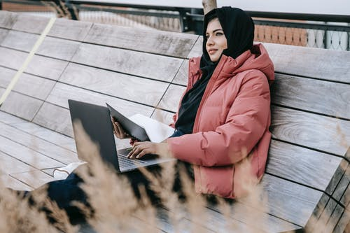 Young ethnic woman in warm clothes and hijab sitting on wooden bench in park and using laptop with notebook in daylight and looking away
