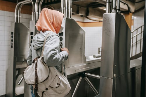 Side view of faceless Muslim female in casual outfit with protective mask and hijab in subway near turnstile with backpack