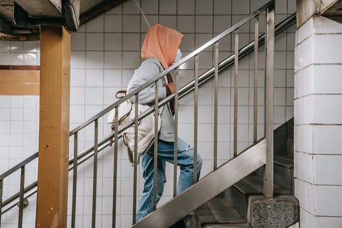 Side view of unrecognizable young Muslim ethnic lady in casual clothes and hijab with protective mask walking on stairs in subway with backpack