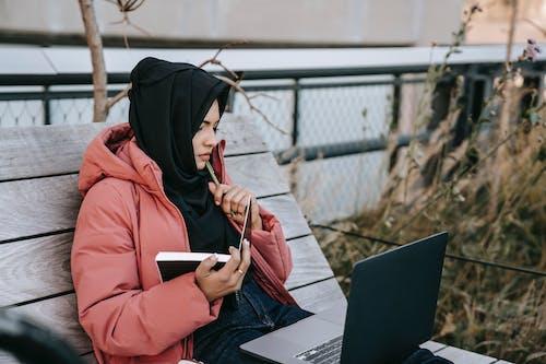 Wanita Berkerudung Merah Menggunakan Smartphone