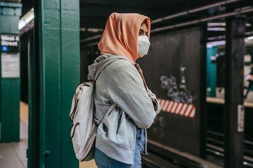 Faceless ethnic female standing in metro in mask