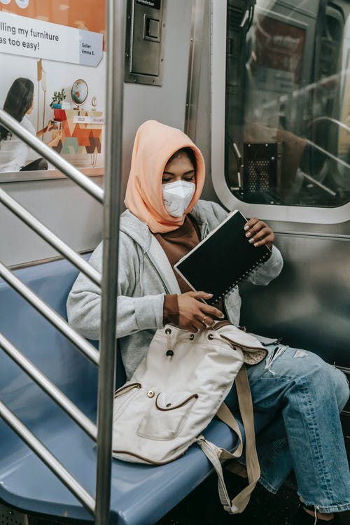 Muslim woman with notepad in underground train