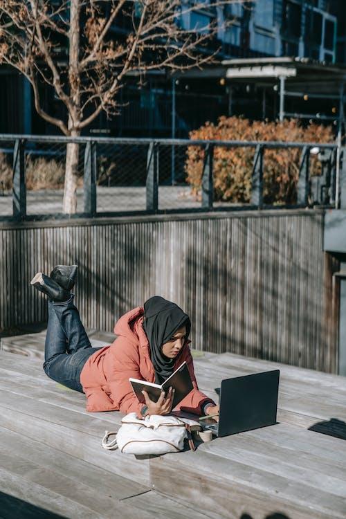 Homme à Capuche Gris Assis Sur Le Sol à L'aide D'un Ordinateur Portable