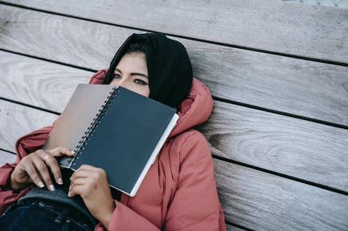 High angle of young Middle East female in casual clothes and traditional headscarf lying on wooden floor of terrace and covering face with notebook