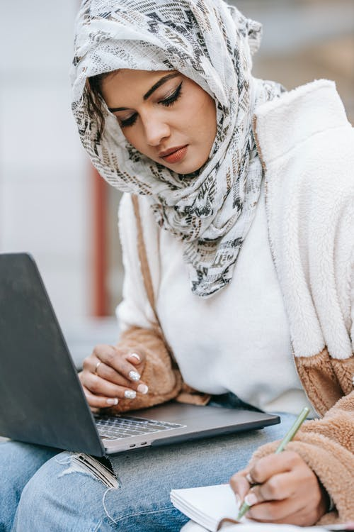 Young ethnic female freelancer in warm outfit and hijab using laptop while making notes in notebook with pen in daytime