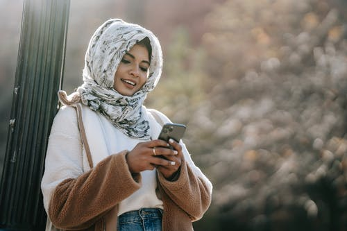 Smiling ethnic young woman in warm outfit and hijab leaning on pillar while text messaging on cellphone in daytime in city street