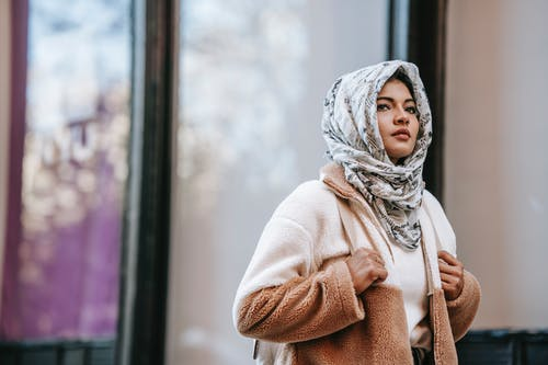 Ethnic female in hijab walking in street