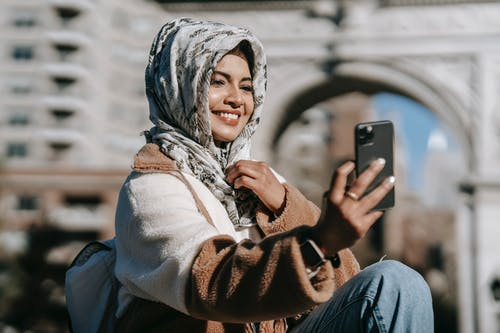 Ethnic woman using mobile in city street