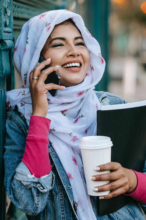 Smiling ethnic young female in casual outfit and hijab speaking on smartphone with cup of coffee and folder with papers while leaning on wall in city street in daytime