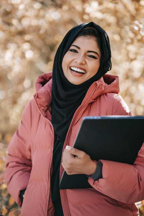 Smiling Middle East woman with laptop in park
