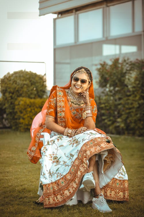 Woman in Orange and White Floral Sari Sitting on Green Grass Field