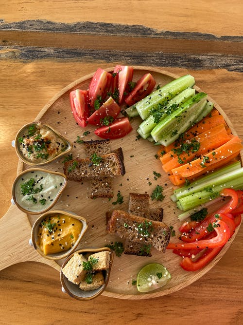 Sliced Assorted Vegetables and Bread on Brown Wooden Tray