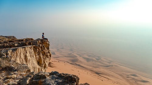Person Standing on Brown Rock Formation