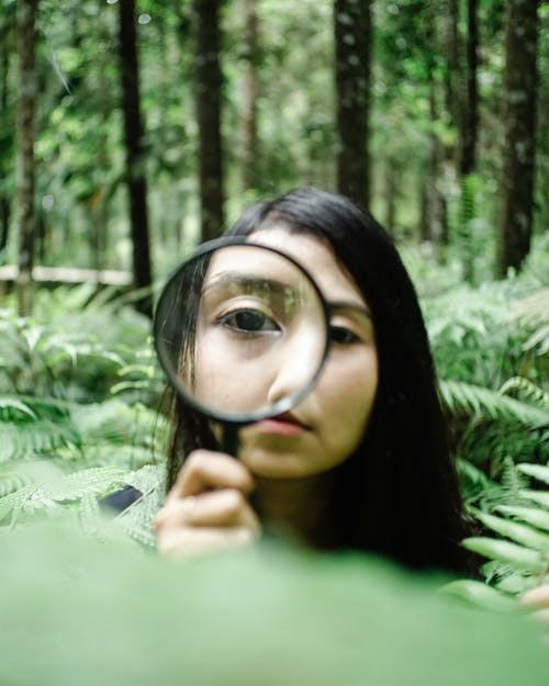 Curious Asian woman with magnifier in forest