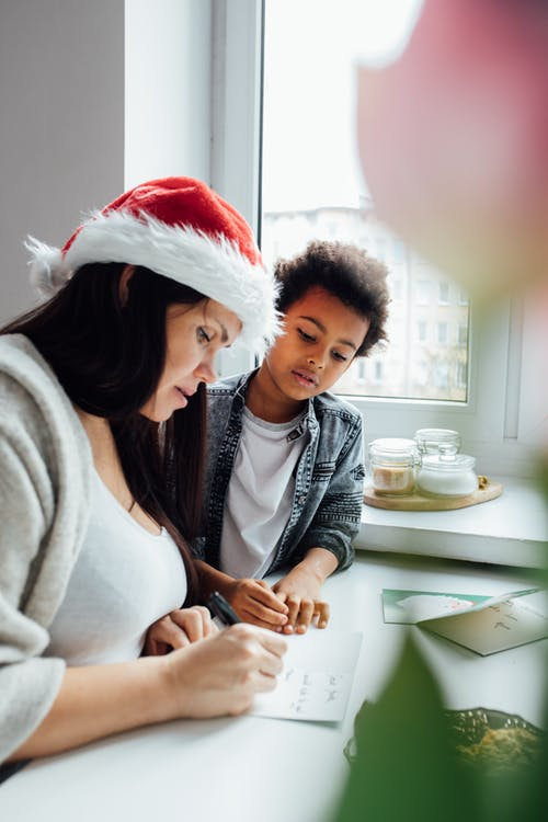 Woman Wearing A Santa Hat Writing A Letter
