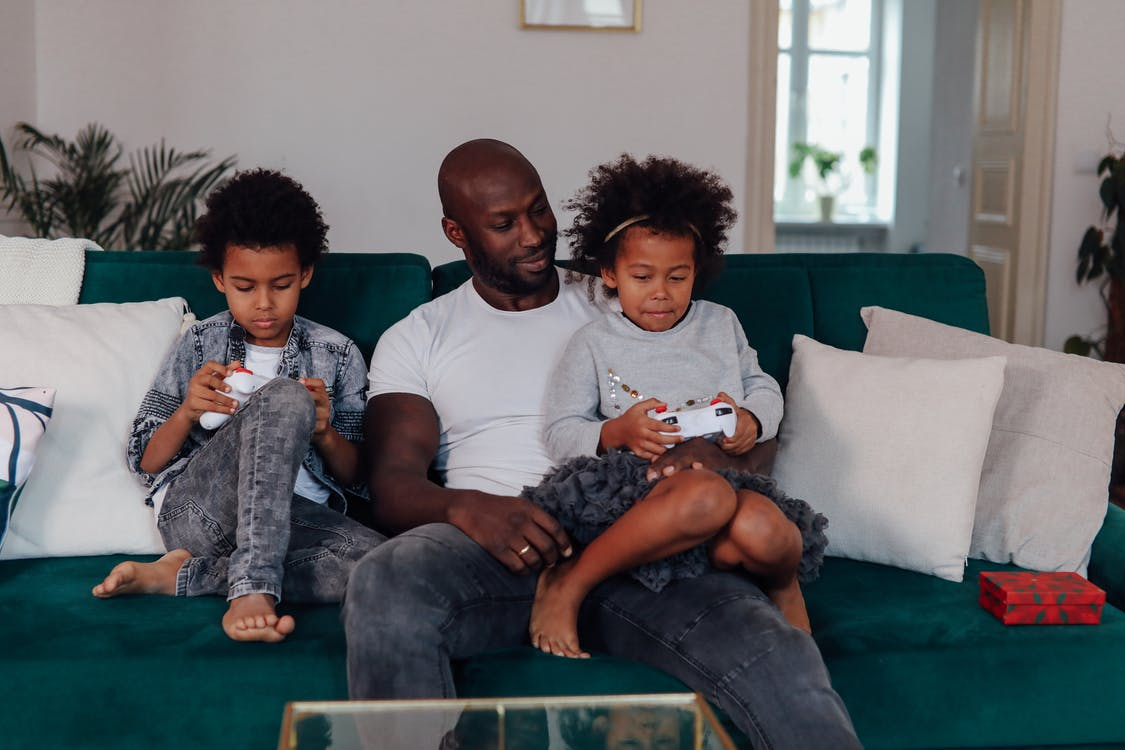Man In White Crew Neck T-shirt Sitting With His Kids