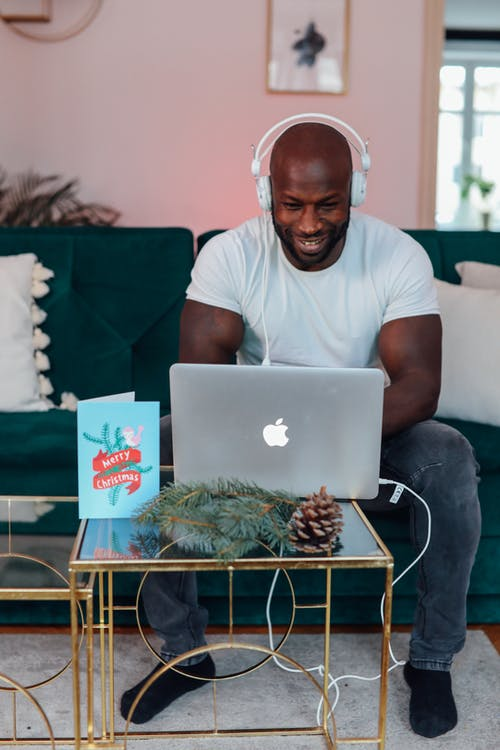 Man In White Crew Neck T-shirt Sitting On A Chair Using Macbook