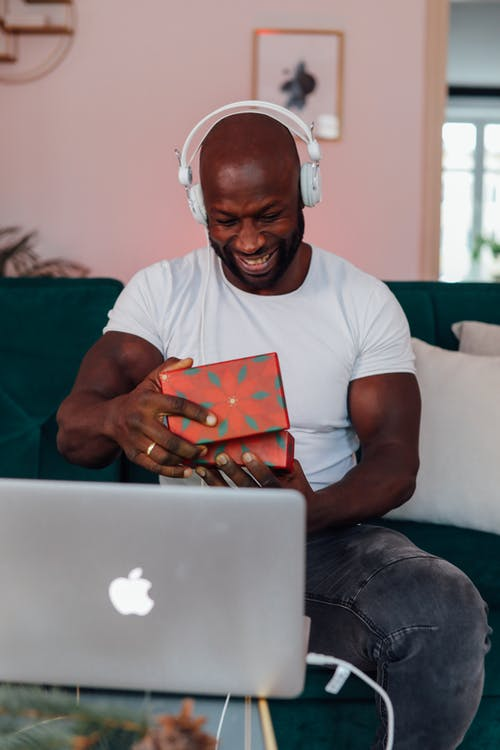 Man In White Crew Neck T-shirt Opening A Gift