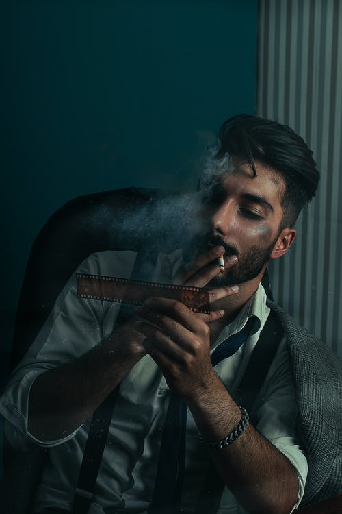 Confident bearded ethnic male detective wearing classy shirt and tie sitting in darkness and smoking cigarette while thoughtfully examining filmstrip