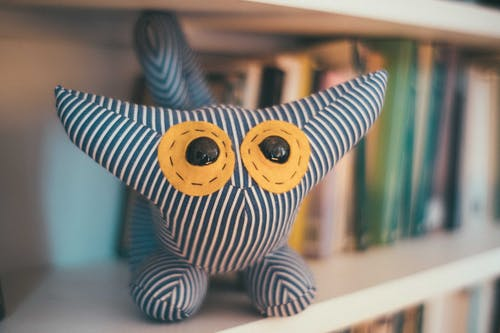 Adorable stuffed toy made of striped fabric placed on bookshelf with abundance of books in light room on blurred background